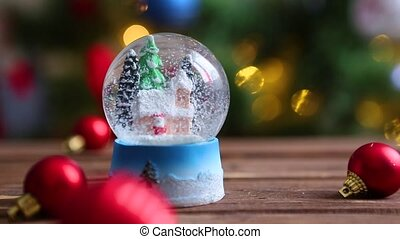 Christmas snow globe on background of christmas tree with christmas lights