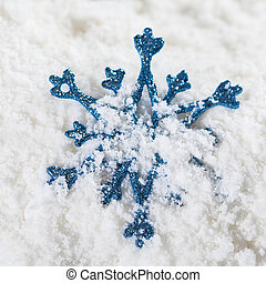 Christmas snowflake bauble decoration on snow.