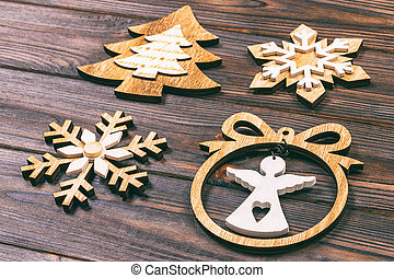 Christmas snowflakes, Christmas tree and angel in a frame on a wooden background. New Year wooden decorations. Toned