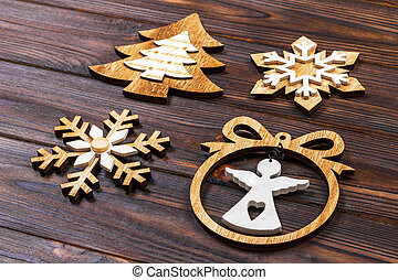 Christmas snowflakes, Christmas tree and angel in a frame on a wooden background. New Year wooden decorations
