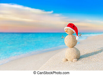 Christmas Snowman in red Santa hat at sunset sea beach -...