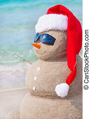 Christmas snowman in santa hat at sandy beach - Sandy...