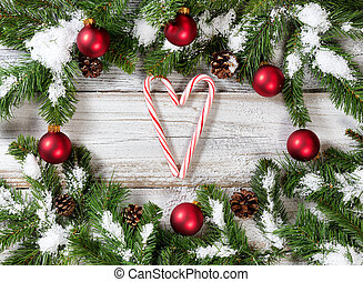 Christmas snowy tree branches with candy canes forming heart...