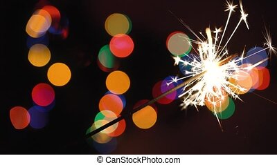 Christmas sparkler burning on a background of christmas tree with colorful bokeh and christmas lights