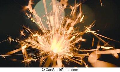 Christmas sparkler burning on a black