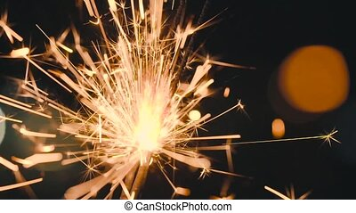 Christmas sparkler burning on a black. Slow motion