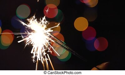 Christmas sparkler burning on a background of christmas tree...