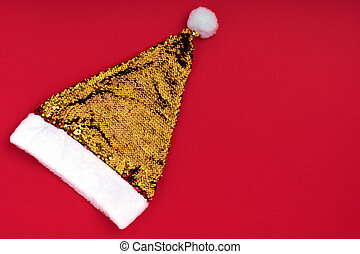 Christmas sparkling golden Santa Claus hat on red background. Top view, flat lay, copy space