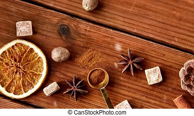 christmas, cooking and seasonal concept - snow falling over aromatic spices on wooden background