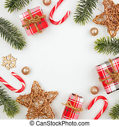 Christmas square frame of gifts, decorations, candy canes and branches on white