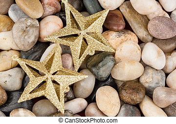Christmas star ornaments on pebbles