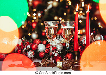 Christmas still life - Two glasses of champagne with Xmas decorations and Christmas tree on blurred background red room