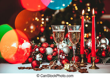 Christmas still life - Two glasses of champagne with Xmas decorations and Christmas tree on blurred red background