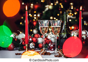 Christmas still life - Two Stemware of champagne with Xmas decorations and Christmas tree on blurred red background