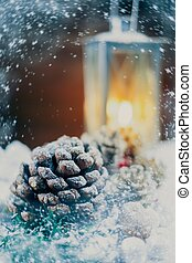 Christmas still life with cones and lantern on a snow