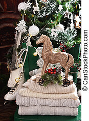 Christmas still life with wool sweaters and vintage wooden horse on green chair