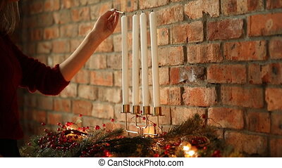 Christmas. Woman lights up candles