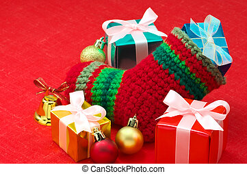 Christmas stocking and colorful christmas presents on red fabric