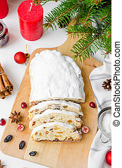 Christmas stollen with mix dried fruits, nuts and icing sugar on the board. Traditional German Christmas Fruit Cake. Close up. Vertical orientation.
