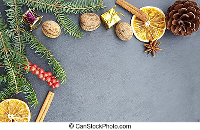 Christmas stone background with fir tree, nuts and spices