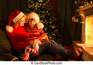 Christmas story time with mother and child in front of fireplace at x-mas tree