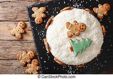 Christmas sweet cake with cheese cream and gingerbread close-up. horizontal top view