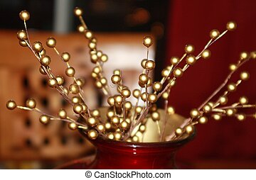 Attractive Christmas table centerpiece with gold holly berries. Dining room chair faded in the background. Holiday decoration for the winter season.