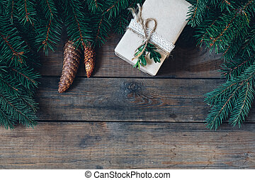 Christmas gift and spruce branch with cones on dark wooden surface