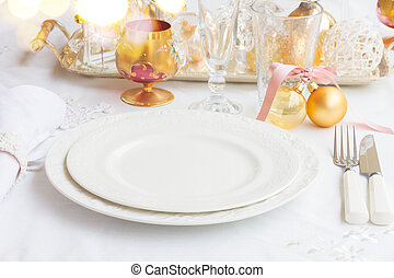 Tableware for christmas - set of empty plates and utencils on white tablecloth with defocused lights in background