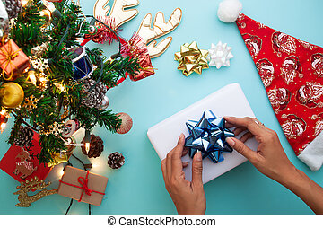 Christmas theme with woman wrapping gift box. Flat lay, top view