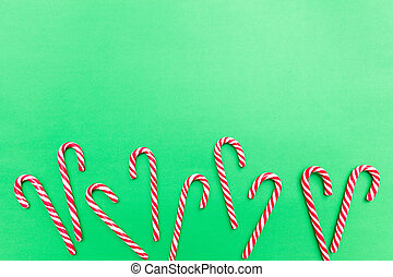 Candy canes on green background, copy space