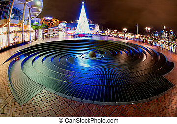 Christmas time in Darling Harbour, Sydney, Australia. Blue christmas tree in front of a rounded fountain.
