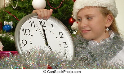 Little girl wearing Santa hat holding ticking clock on background of Christmas tree