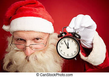 Christmas time - Smiling Santa showing alarm clock with five...