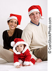 Christmas togetherness - Young couple with baby dressed in...