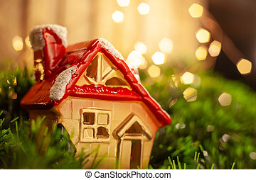 Christmas toy figurine house in green tinsel on the background of a garland