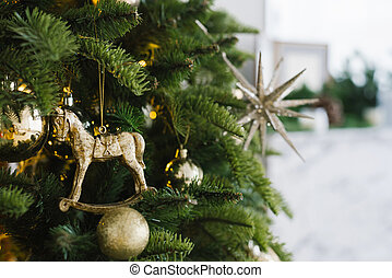Christmas toy horse and balls hang on the tree, decorated with lights. Copy space