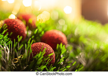 Christmas toy red shiny balls lie in a green tinsel in the background of a garland