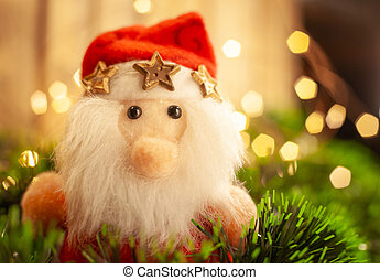Christmas toy Santa Claus in green tinsel against the background of a garland