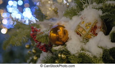 Christmas toys hanging on the Christmas tree. Colored garland. The city is decorated for Christmas.