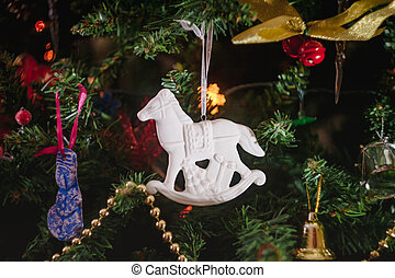 Christmas toys in the form of a white ceramic antique rocking horse with gifts on a decorated Christmas tree. Close-up.