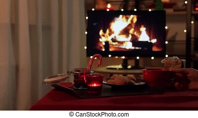 winter holidays and hygge concept - hand placing cup of coffee or hot chocolate to table with ginger cookies, candle, candy canes and gift boxes over tv monitor used as fireplace at cozy home