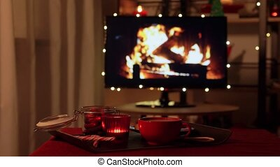 winter holidays, christmas and interior concept - cup of coffee or hot chocolate, cookies, candle and candy canes on table over tv monitor used as fireplace in decorated dark living room at cozy home