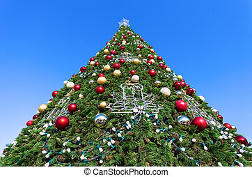 Christmas tree against the blue sky background
