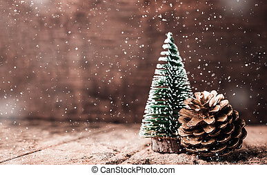 Christmas tree and gold pine cone and snow falling on grunge wood table and dark brown wooden wall. Winter Merry Christmas holiday greeting card.