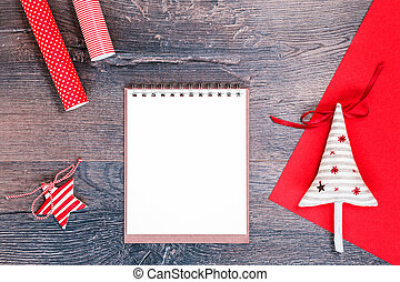 Christmas tree and red gift wrapping paper and notebook