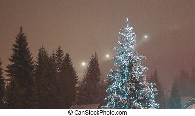 Christmas tree and snow falling in a forest background