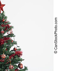 detail of a christmas tree decorated with red garland, globes and star isolated on white background framed in the left border of the image