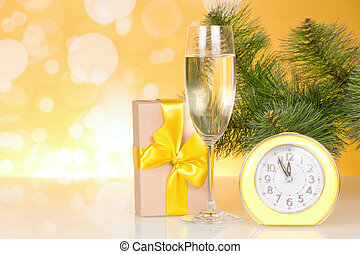 Christmas-tree branch, a glass of champagne, gift box and about twelve hours