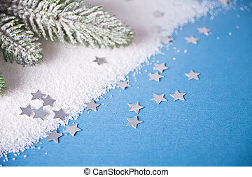 Christmas tree branch on the blue background with small snowflakes